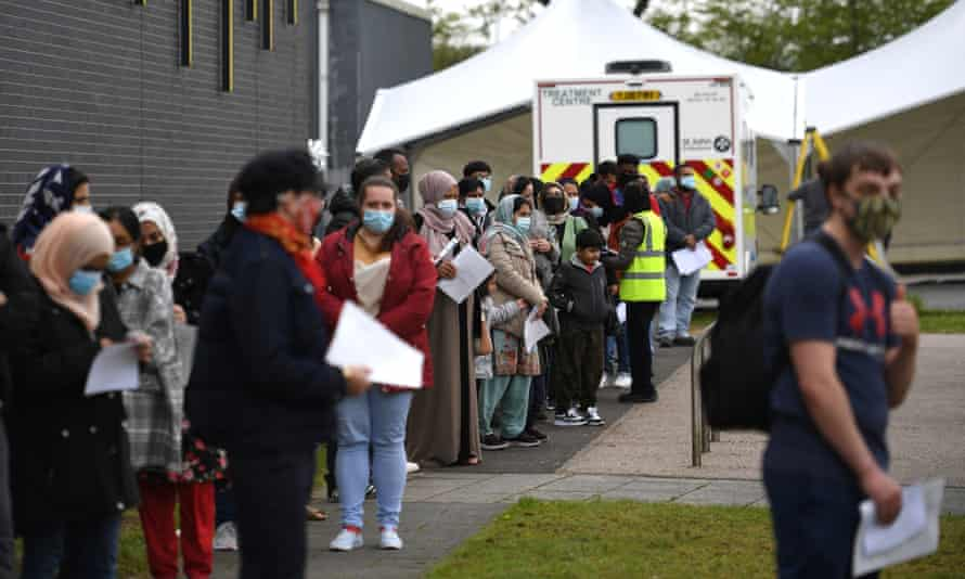 Members of the public queue at a temporary Covid-19 vaccination centre in Bolton on 14 May.