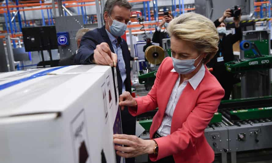 European commission President Ursula von der Leyen places an EU flag sticker on a box of Pfizer Covid-19 vaccines during an official visit to the Pfizer pharmaceutical company in Puurs, Belgium, Friday, April 23, 2021. (John Thys, Pool via AP)