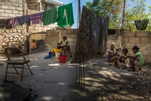 Paul Lfanie, 40, washes clothes on her porch while her children play a board game in the background