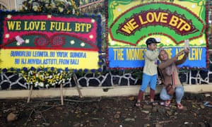 """Supporters of former Jakarta governor Basuki """"Ahok"""" Tjahaja Purnama, take a selfie in front of wreaths sent by well-wishers outside a police prison in Depok, Indonesia, on Thursday."""