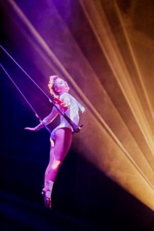 an acrobat swings on a trapeze