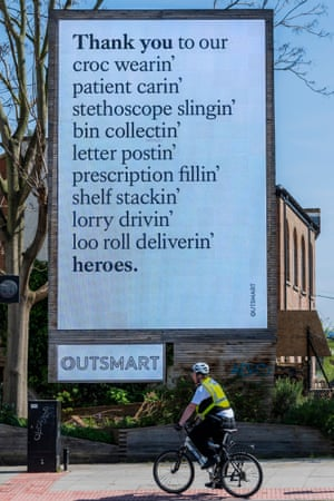 A cycle police officer passes a rhyming message of thanks to key workers organised by the Out of Home advertising industry near St Thomas' Hospital.