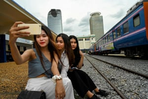 Posing for selfies next to a train.