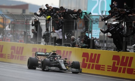 Lewis Hamilton crosses the finish line to win the Turkish Grand Prix as his team celebrate at trackside