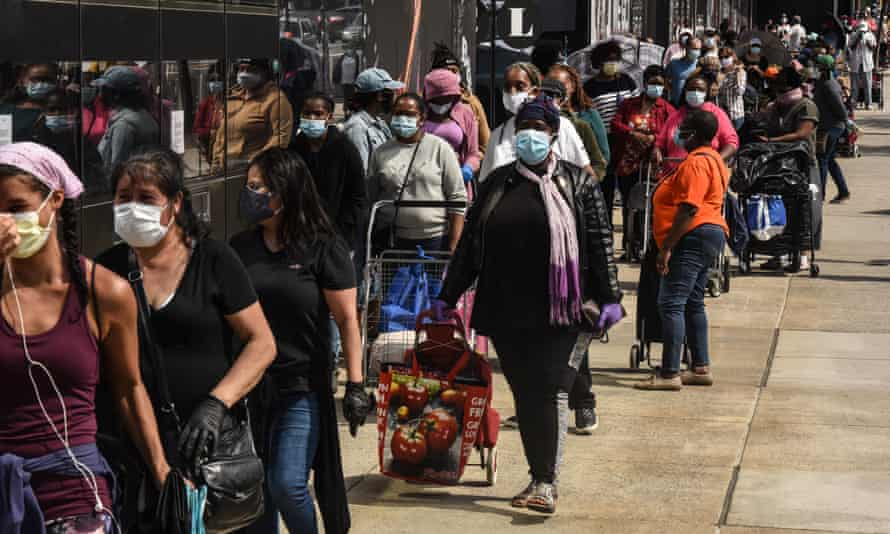 New Yorkers queue at a food bank in the Barclays Center, Brooklyn, last week.