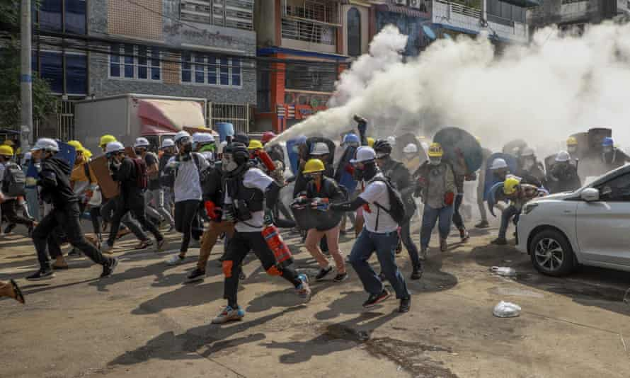 Anti-coup protesters run as one of them discharges a fire extinguisher