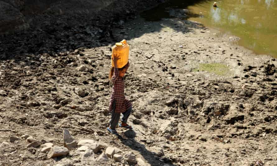 An Indian girl carries drinking water in a plastic container near Jammu, India. Millions don't have enough water amid a weeks-long drought.