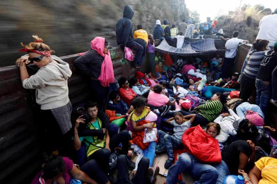 Central American migrants, moving in a caravan through Mexico, journey an open wagon of a freight train after stopping it on the rail line, in Hidalgo state, 14 April
