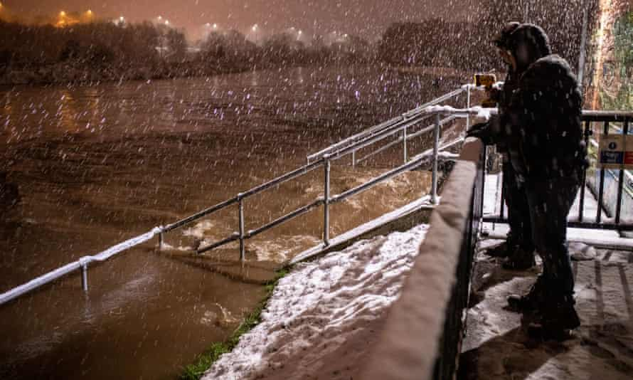 Residents in Didsbury in south Manchester assess the water levels of the River Mersey and its overflows as they decide whether to evacuate their homes