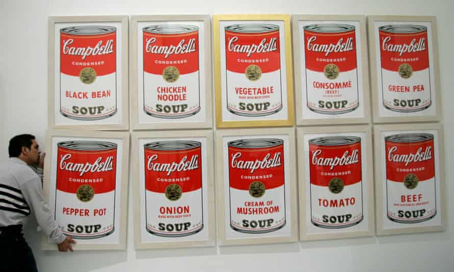 Satirising consumerism … a worker hanging Campbell's Soup by Andy Warhol.