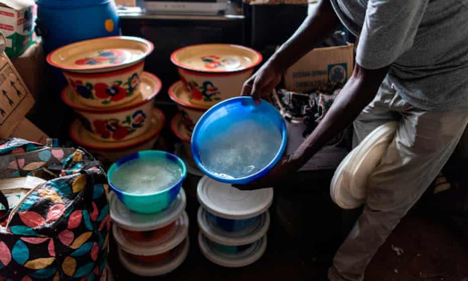 A National Drug Law Enforcement Agency official with one of 18 tubs of methamphetamine found at a lab in a village in south-east Nigeria