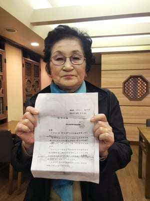 Kim Jung-im holds the service record of her father, who was conscripted into the Japanese imperial army and died in New Guinea in 1943.
