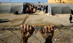 A Kurdish boy from the Syrian town of Kobani holds on to the fence at a refugee camp in Sanliurfa province