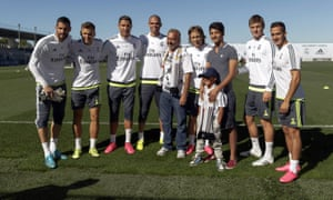 Osama Abdul Mohsen (C) and his sons Mohammad (3rd R) and Zaid (3rd R front) pose with Real Madrid players.