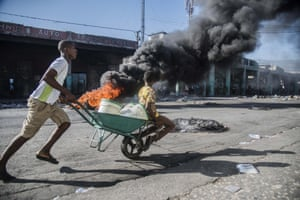Port-au-Prince, Haiti. A pushes a child in a wheelbarrow near a burning tyre barricade during protests against an increase in fuel prices