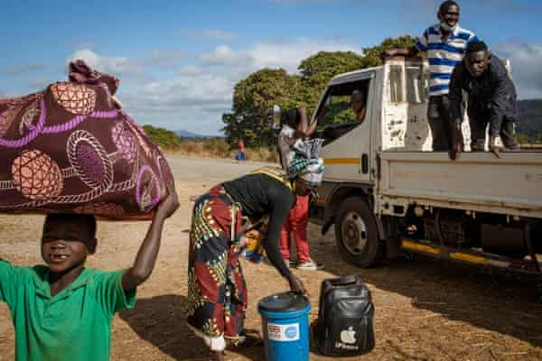Displaced people climb out of a pick up truck Cabo Delgado.