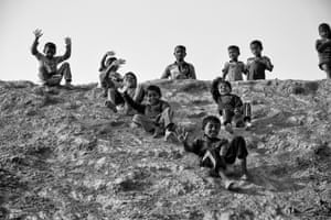 Cox's Bazar, BangladeshRohingya children slide down a hill on plastic canisters in Kutupalong refugee camp. Over 655,000 Rohingya have arrived in the area since August 2017 fleeing persecution in neighbouring Myanmar