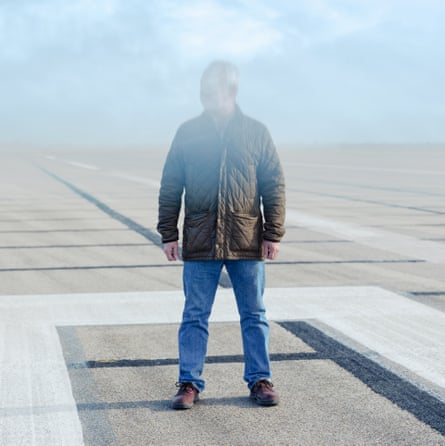 Alan Irwin on a runway with his face obscured by smoke
