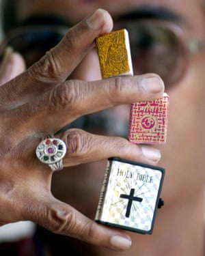 Jagadish Shukla, a magician, holds his miniature copies of a Koran, the Bhagavad Gita and the Bible in Bangalore in 2001.
