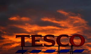 the sun sets above a Tesco supermarket