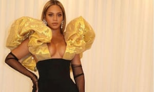 Beyoncé wears sheer opera gloves with her Schiaparelli gown to the Golden Globes.