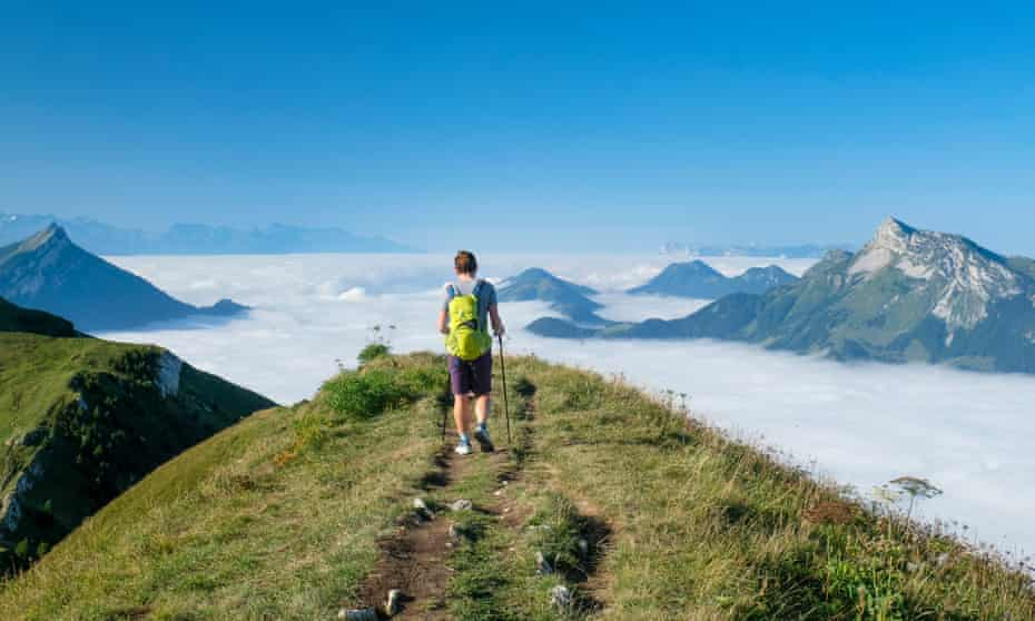 Hiker on a ridge of Mont Trélod on a blue-sky day. He is above the clouds and surrounded by mountain peaks in the French Alps.