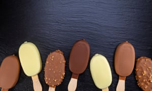 Ice cream on stick covered with chocolate on black stone slate board.