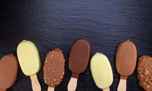 Ice cream on stick covered with chocolate on black stone slate board