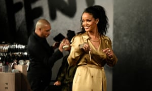Rihanna wears a Burberry trench on stage at a Fenty Beauty event.