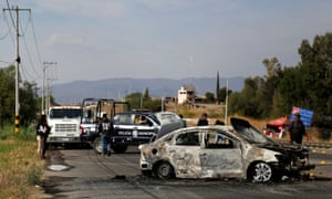 Police stand by the wreckage of a burned-out car on the outskirts on Celaya in Guanajuato. A top analyst said it was 'business as usual' for the cartels.