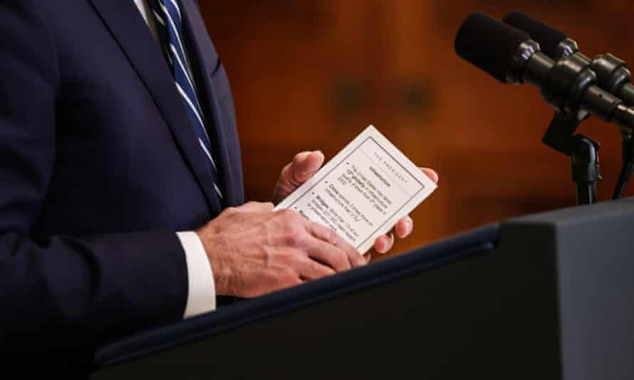 Joe Biden holds a note card as he delivers remarks during the first formal press conference of his presidency.