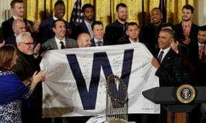 Obama – a White Sox fan – accepts a signed 'W' flag from the Cubs.