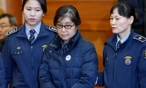 Police officers flank Choi Soon-sil, the woman at the centre of the South Korean political scandal and long-time friend of Park Geun-hye.