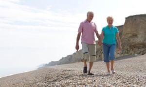mature couple walking on shingle beach.