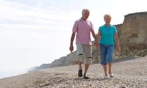 Mature couple walking on shingle beach