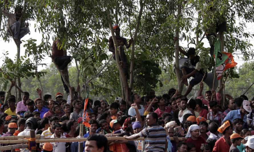 People climb trees to get a better view of a rally addressed by Modi in Mathurapur, West Bengal.