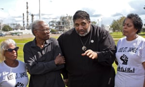 Rev William Barber stands at the entrance of the Ponchartrain Works facility in Reserve, Louisiana, flanked by Robert Taylor, director, Concerned Citizens of St John the Baptist and Sharon Lavigne, president, St James Rise