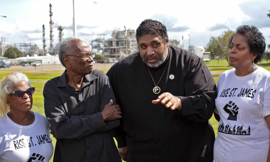 The Rev William Barber at the entrance of the Ponchartrain Works facility in Reserve, Louisiana, with Robert Taylor and Sharon Lavigne.