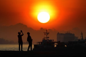People take photos of the sunrise in Singapore
