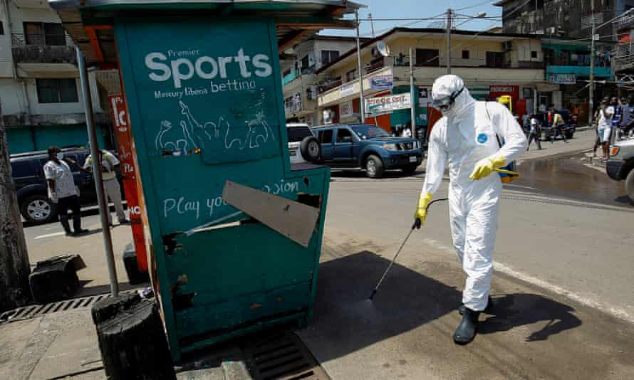 A health worker disinfects a street corner where a suspected Ebola patient was picked up and taken into an ambulance in Monrovia, Liberi