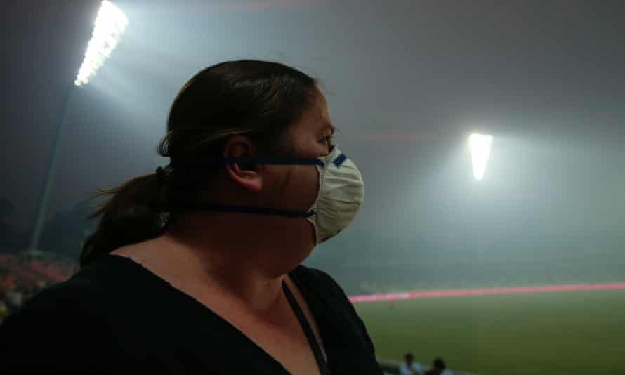 A member of the crowd looks on as smoke haze forces a stoppage in play during the Big Bash match between the Sydney Thunder and Adelaide Strikers in Canberra.