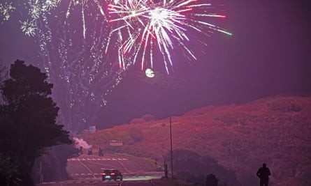 People set off Guy Fawkes Night fireworks at Bracelet Bay car park in Swansea under a waning gibbous moon.