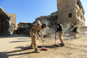People clean streets in Mosul, Iraq