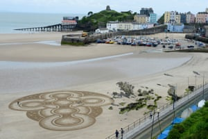 Pembrokeshire, Wales Sand artist Marc Treanor creates a work on the north beach at Tenby harbour
