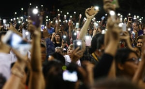El Paso, Texas: People hold up their phones in lieu of candles at an interfaith vigil