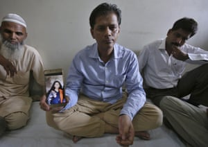 Abdul Aziz Sheikh, shows a picture of his daughter in Karachi, Pakistan.