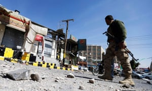 A Houthi fighter walks past damaged shops outside a barracks on a mountain overlooking the presidential palace in Sana'a.