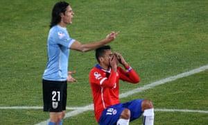 Gonzalo Jara falls to the floor after minimal contact from Uruguay's Edinson Cavani.