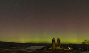 The northern lights shine behind a barn and silos in Pine Bush, New York