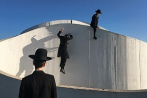 Jewish orthodox youths climbing on a building